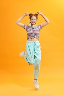 Young beautiful energy girl with white headphones listening to music laughs and jump on yellow background