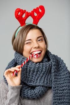Молодая красивая белокурая женщина в больших вязаных шарф и оленей рождественский рога, улыбаясь, ест полосатый леденец на сером.