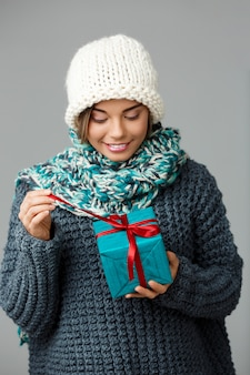 Young beautiful fair-haired woman in knited hat sweater and scarf smiling opening gift box on grey.