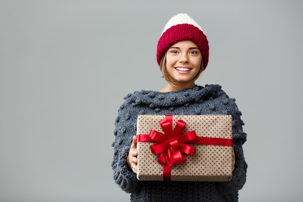 Young beautiful fair-haired woman in knited hat and sweater smiling holding gift box on grey.