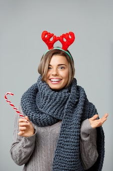 Young beautiful fair-haired woman in large knited scarf and christmas reindeer antlers smiling eating striped lollypop on grey.