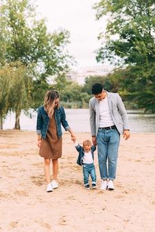 湖の近くで素晴らしい時間を過ごしている若い美しい家族