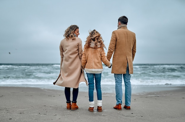 Young beautiful family look at the sea holding hands, dressed in scarves and coats in winter.
