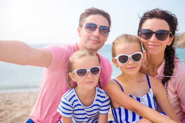 Young beautiful family taking selfie on the beach