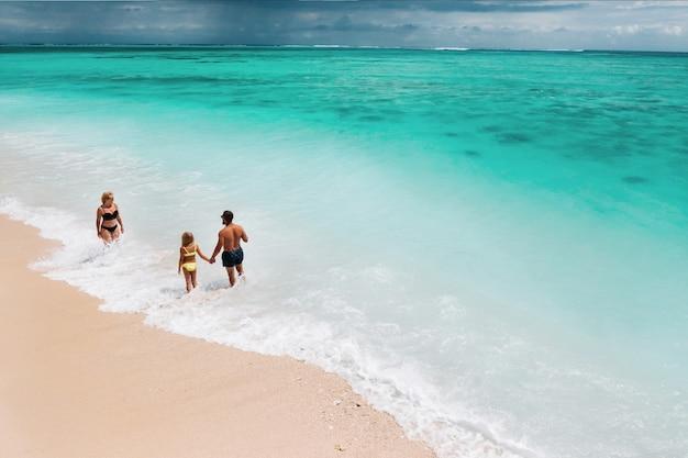 Молодая красивая семья с ребенком на острове маврикий тропический отдых.