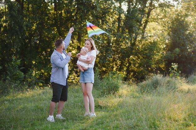 小さな娘と若い美しい家族は、日没時に抱きしめ、キスし、自然の中を歩きます。自然の中で小さな子供を持つ家族の写真。