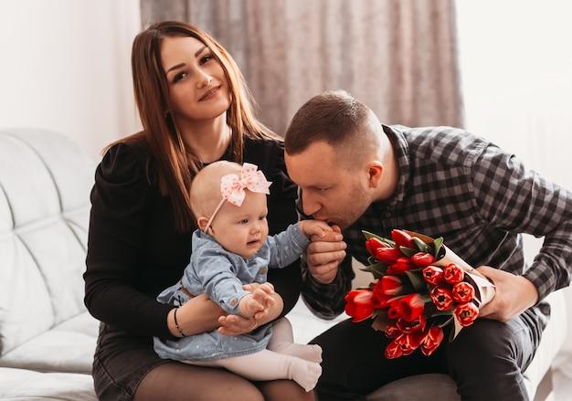 花の花束とソファの上に小さな娘を持つ若い美しい家族。父親は女児の手にキスをします。母の日