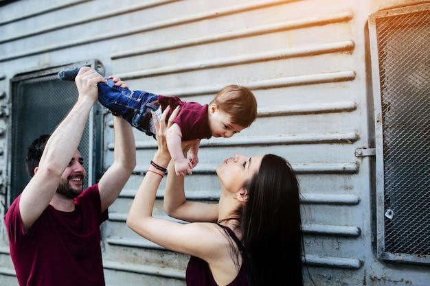 Молодая красивая семья с ребенком позирует на серой стене