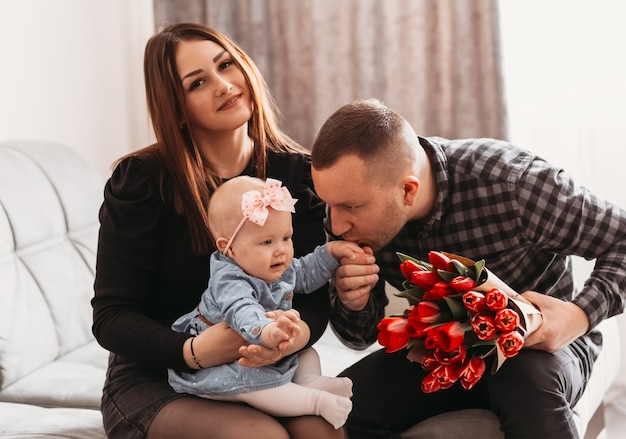 Young beautiful family with a little daughter on the couch with a bouquet of flowers. the father kisses the hand of the girl infant. mother's day