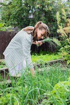 手に新鮮な収穫ハーブを持つ若い美しい農家
