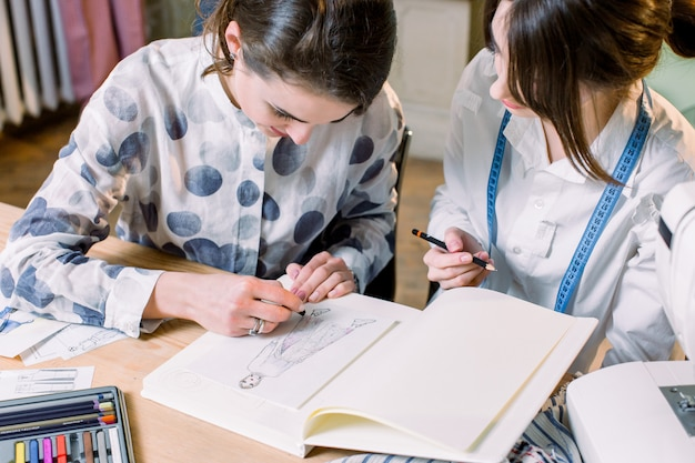 Young Women Working As Fashion Designer Drawing Sketches For Clothes In Atelier Paper At Workplace Studio Premium Photo