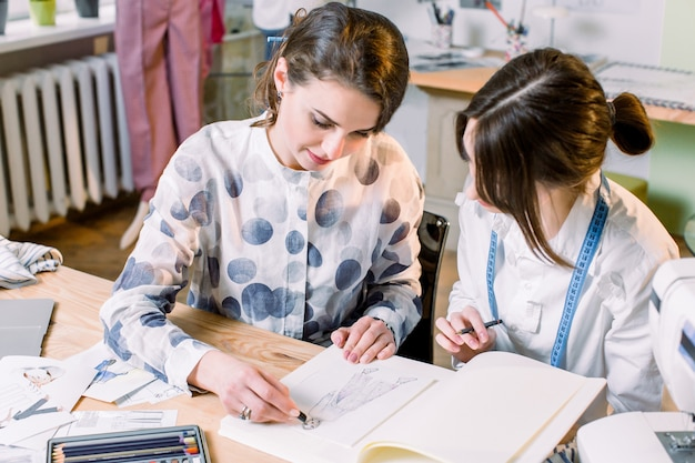 Young beautiful fashion designer and dressmaker in fashion atelier drawing sketch of stylish pants. the process of designing clothes.