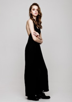 Young beautiful fashion model wearing black dress on grey