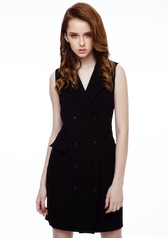Young beautiful fashion model wearing black dress with no sleeves on white