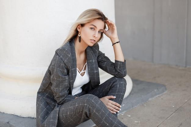 거리에 흰색 향수 근처에 앉아 세련된 빈티지 회색 정장에 젊은 아름 다운 패션 모델 여자