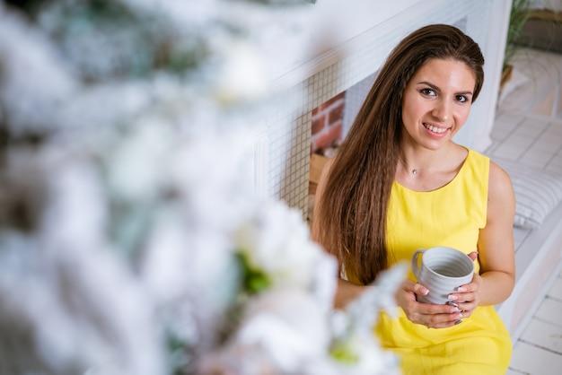 彼女の手のファッションの美しさでマグカップとクリスマスツリーの近くの黄色のドレスで若い美しいファッションの女性...