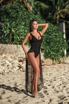 Молодая красивая модная женщина в купальнике и накидке из черного кружева отдыхает летом на курорте
