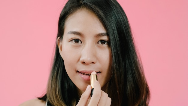 Young beautiful fashionable asian woman applying lips makeup with cosmetic brush in casual clothing over pink background studio shot.