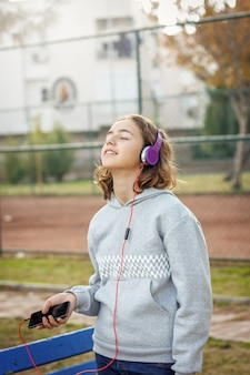Young beautiful fashionable teenager girl listens to music on headphones from a smartphone