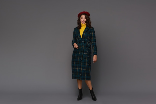 トレンディな秋のコート、赤いベレー帽と灰色の背景で隔離の黄色いセーターの若い美しいファッショナブルな女性。
