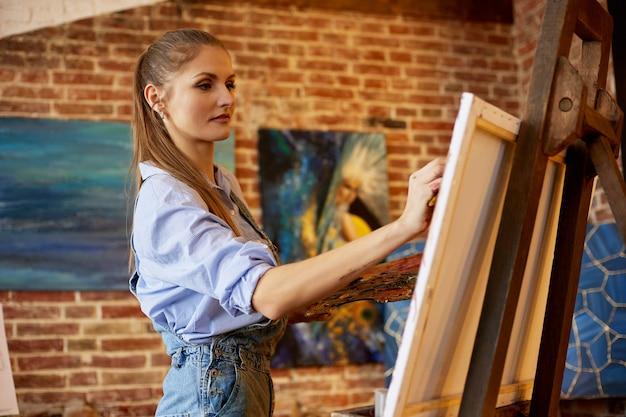 油絵とアートブラシ画家の作成を使用してキャンバスに絵を描く若い美しい女性アーティスト...