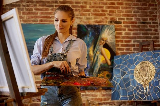 油絵とパレットナイフペインタークリエイトを使用してキャンバスに絵を描く若い美しい女性アーティスト...