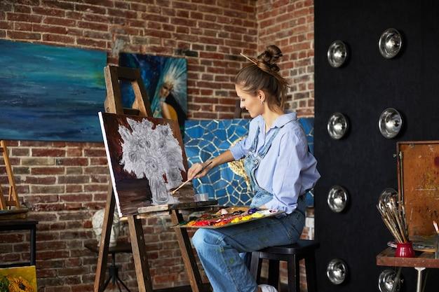 油絵と...を使用してキャンバスにひまわりと静物を描く若い美しい女性アーティスト