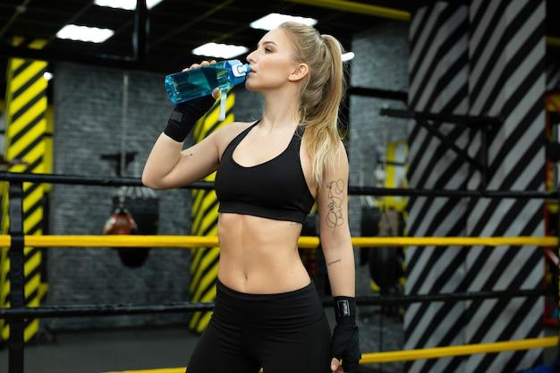 아름 다운 젊은 여자 선수는 병에서 물을 마신다