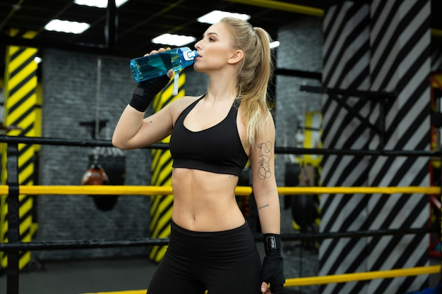 Young beautiful female athlete drinks water from a bottle
