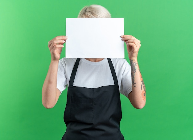 Young beautiful female barber in uniform covered face with papper isolated on green background