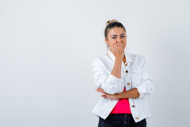 若い美しい女性は、tシャツ、白いジャケット、動揺して釘を噛んでいます。正面図。