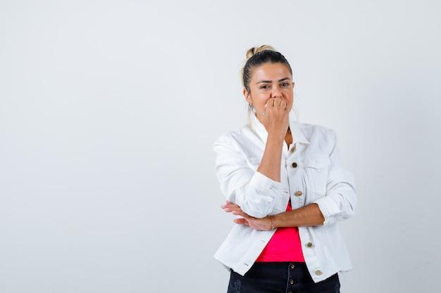 Giovane bella femmina che morde le unghie in maglietta, giacca bianca e sembra sconvolta. vista frontale.