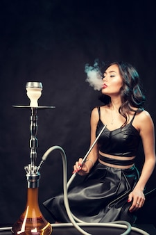 Young beautiful female in black dress smoking and exhales hookah
