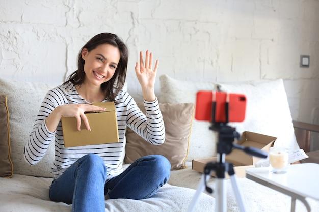 自宅で荷物を開梱しながらビデオを録画する若い美しい女性ブロガー。