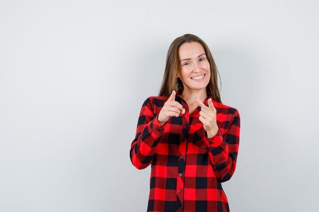 Giovane bella donna in camicia casual che punta alla telecamera e sembra felice, vista frontale.