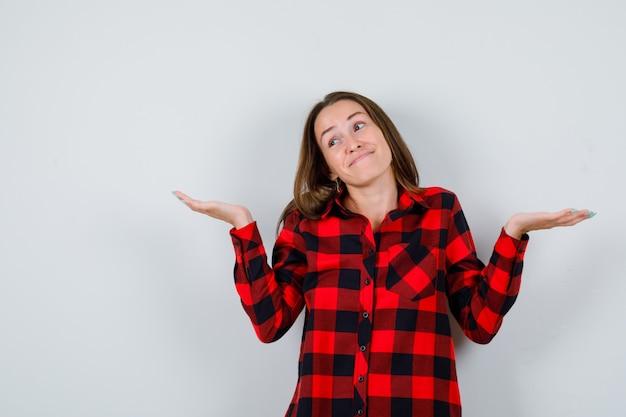 Giovane bella donna in camicia casual che mostra gesto impotente e sembra allegra, vista frontale.