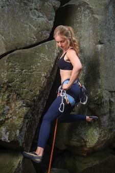 큰 바위를 등반 하 고 carbines를 들고 젊은 아름 다운 여성 산악인. 여름날