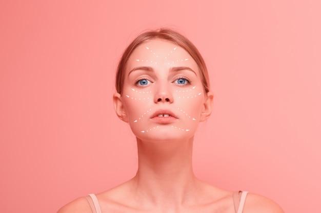 젊은 아름 다운 여성은 그녀의 얼굴에 화살표가있는 얼굴 초상화를 닫습니다