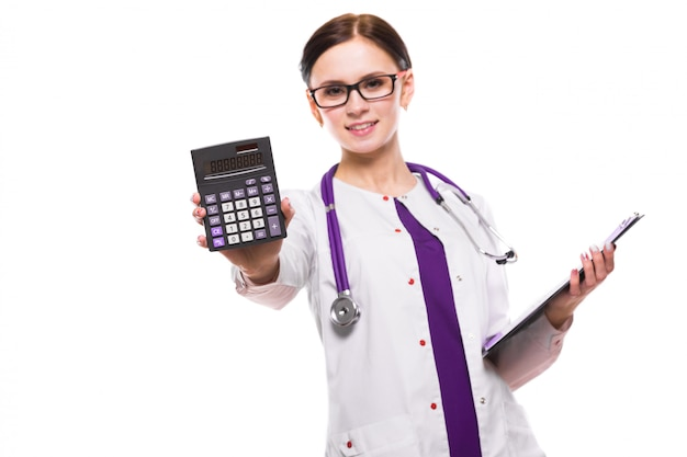 Young beautiful female doctor holding clipboard and showing calculator in her hands on white