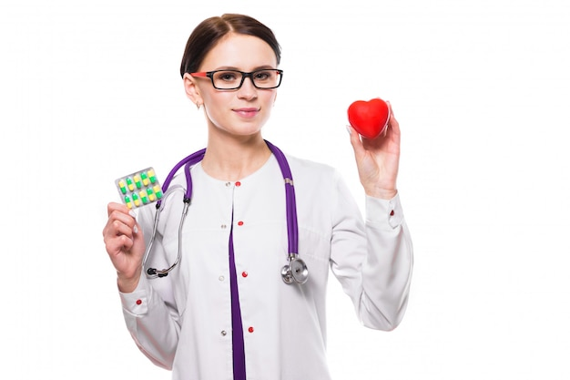 Young beautiful female doctor holding heart and pills in her hands on white background