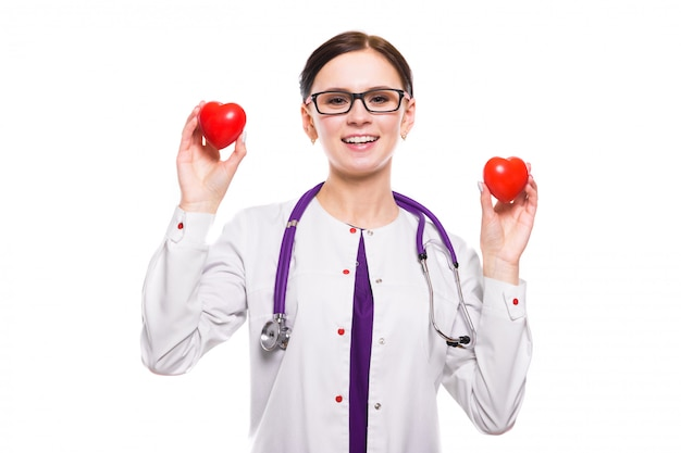 Young beautiful female doctor holding hearts in her hands on white
