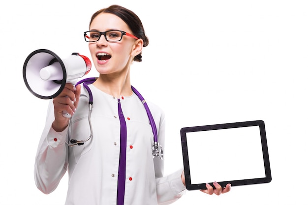 Young beautiful female doctor holding tablet in her hands speak in megaphone