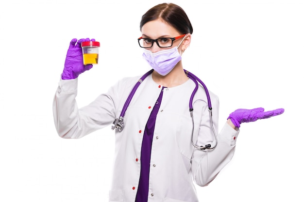 Young beautiful female doctor holding urine sample in her hands in medical mask and sterile gloves