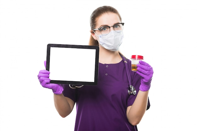 Young beautiful female doctor holding urine sample and tablet in her hands in medical mask and sterile gloves on white