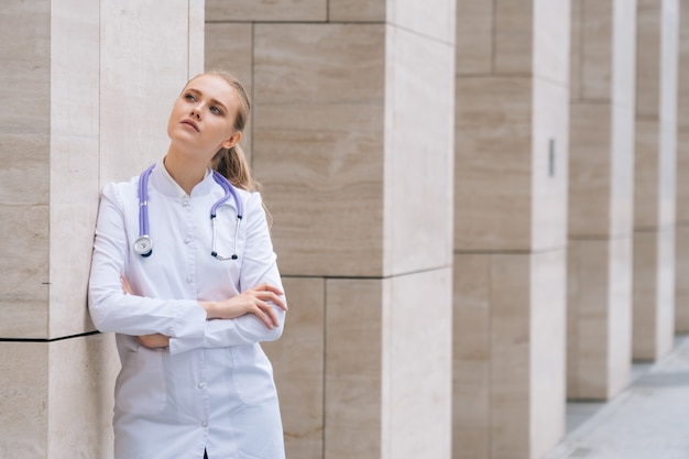 A young beautiful female doctor holds a stethoscope on an isolated white space.
