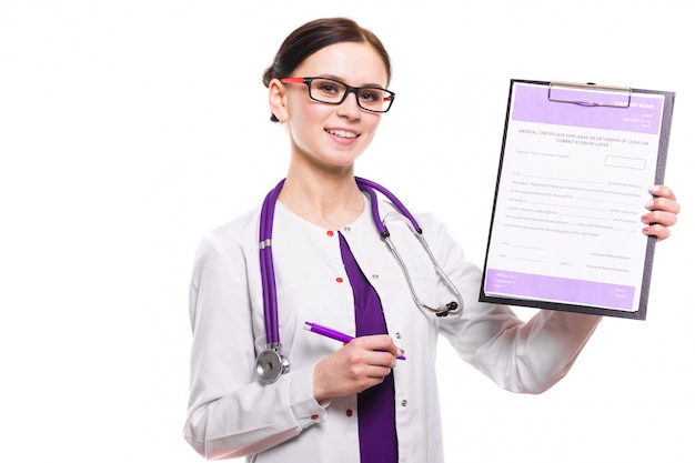 Young beautiful female doctor showing on clipboard with pen on white