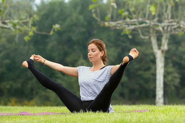 Young beautiful female doing yoga exercise outdoors