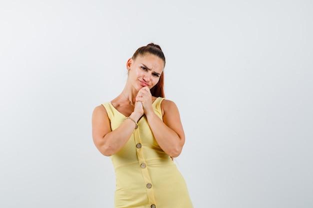 Giovane bella femmina in abito tenendo le mani giunte sotto il mento e guardando sconvolto, vista frontale.