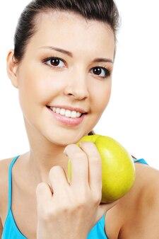 Молодое красивое женское лицо с зеленым яблоком - крупный план