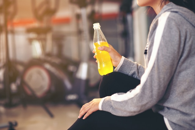 Young beautiful female fitness indoor holding water bottle